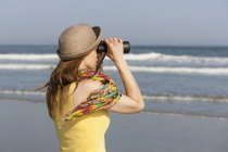Woman in sunhat and scarf using binoculars on beach on New Jersey Shore, USA. — Stock Photo