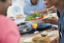 Close-up of people talking and handing plates of food across buffet table. — Stock Photo