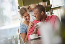 Woman leaning on shoulder of man having coffee in cafe interior. — Stock Photo