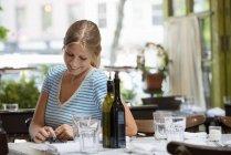 Femme en t-shirt rayé assis à table de café et de vérification de smartphone. — Photo de stock