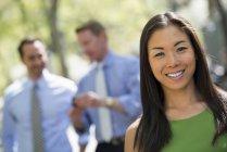 Mid femme adulte souriant et regardant à huis clos avec des hommes d'affaires parler en arrière-plan. — Photo de stock