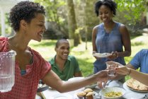 Friends and family gathering around dinner table in countryside garden. — Stock Photo