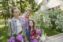 Mature woman with teenager and elementary age daughters standing in garden with flowers. — Stock Photo