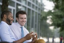 Two businessmen looking at smartphone while sitting on bench in downtown. — Stock Photo