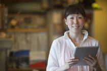 Asiatische Frau hält digital-Tablette und unter Ausschluss der Öffentlichkeit im Haus suchen — Stockfoto