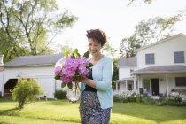Женщина, перевозящих букет цветов рододендрона и улыбаясь в саду — стоковое фото