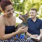 Milieu couple adulte au repos avec chien chihuahua dans le parc. — Photo de stock