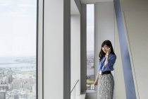 Japanese businesswoman talking on phone in office building. — Stock Photo