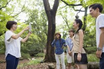Mid adult woman taking picture with digital tablet of friends in forest. — Stock Photo