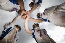 Visão de baixo ângulo do grupo de jovens jogadores de futebol em uniformes esportivos e capacetes protetores . — Fotografia de Stock