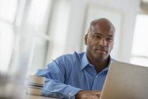 Homem adulto médio sentado na mesa no escritório e usando laptop . — Fotografia de Stock