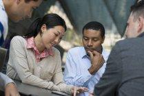 Cuatro personas se reunieron alrededor de la mesa en la ciudad y compartir juntos la tableta digital - foto de stock