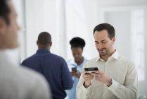 Kleine Gruppe von Menschen, die Smartphones in Bürogebäuden benutzen. — Stockfoto