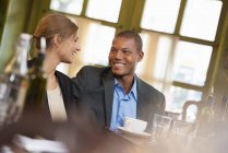 Businessman and businesswoman sitting in coffee shop side by side. — Stock Photo