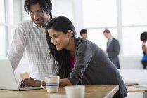 Uomo maturo e giovane donna che utilizza il computer portatile alla scrivania con una tazza di caffè . — Foto stock