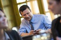 Средний взрослый мужчина сидит за столом кафе и использовании смартфон с людьми на переднем плане. — стоковое фото