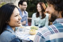 Man and woman looking at each other while gathering with friends around table. — Stock Photo