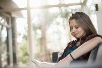 Donna sorridente seduta sul divano e libro di lettura . — Foto stock