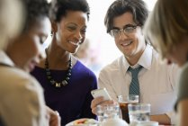 Man and woman sharing smartphone at restaurant table with friends. — Stock Photo