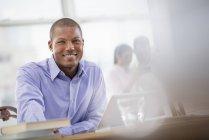 Jeune homme en chemise bleue assis au bureau avec ordinateur portable au bureau . — Photo de stock