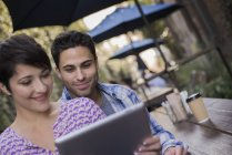 Couple sitting at city cafe and sharing digital tablet. — Stock Photo