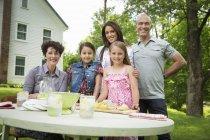 Reunião de família na mesa de jardim e fazendo limonada fresca — Fotografia de Stock
