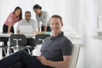 Мужчина сидит на офисном кресле с коллегами, используя ноутбук на заднем плане . — стоковое фото