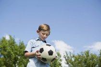 Garçon d'âge élémentaire tenant ballon de soccer dans le parc, vue faible angle — Photo de stock