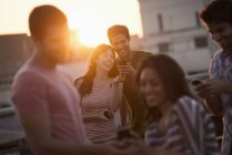 Young friends sharing smartphones on rooftop terrace party. — Stockfoto
