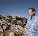Homme debout en face de la maison sur une colline rocheuse du paysage désertique. — Photo de stock