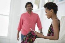Mulher adulta média sentada no sofá branco e usando tablet digital com homem maduro andando em segundo plano . — Fotografia de Stock