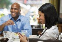 Frau lächelt beim Telefonieren am Kaffeetisch, Mann isst im Hintergrund. — Stockfoto