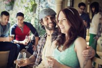 Man and woman drinking win with fiends at house party. — Stock Photo