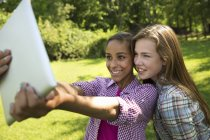 Two girls using digital tablet and taking selfie outdoors. — Stock Photo
