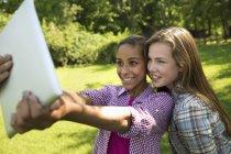 Deux filles à l'aide de tablette numérique et prise selfie à l'extérieur. — Photo de stock