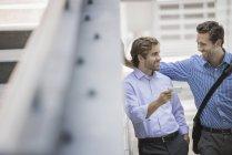 Dois homens de negócios em pé na rua urbana e usando smartphone . — Fotografia de Stock