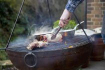 Close-up of man using tongs while roasting bird pieces on barbecue. — Stock Photo