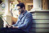 Человек с цифровым планшетом на крыльце в загородном доме . — стоковое фото