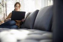 Женщина сидит на диване и держит ноутбук . — стоковое фото