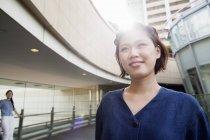 Junge Frau spaziert mit weichem Gegenlicht im Innenhof eines Bürogebäudes. — Stockfoto