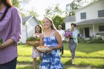 Parents and children walking across lawn carrying flowers, fresh vegetables and fruits. — Stock Photo