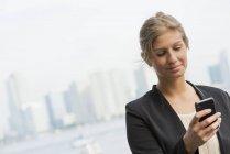 Jovem empresária de jaqueta preta usando smartphone no centro da cidade . — Fotografia de Stock