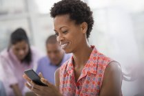 Smiling woman using smartphone with colleagues in background. — Stockfoto