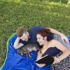 Casal relaxante no tapete azul com chihuahua cão enquanto mulher segurando tablet digital . — Fotografia de Stock