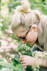 Женщина в солнцезащитных очках наклоняется, чтобы осмотреть цветы . — стоковое фото