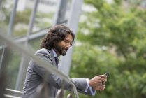 Side view of man in suit leaning on street railing and using phone. — Stock Photo