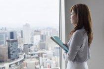 Vista laterale della donna d'affari che tiene i file e guarda attraverso la finestra nell'edificio per uffici . — Foto stock