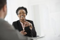 Mulher em um terno preto, falando com o homem na mesa no escritório — Fotografia de Stock