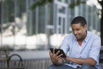 Africano americano sentado no banco e segurando tablet digital . — Fotografia de Stock