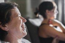 Duas mulheres no perfil sentado dentro de casa e rir — Fotografia de Stock